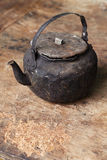 Sooty old teapot  on old table in open kitchen Royalty Free Stock Photo