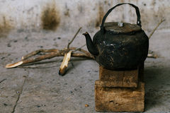 Sooty old teapot  on small wooden bench in open kitchen Royalty Free Stock Images