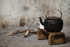 Sooty old teapot and white enamel mug. On small wooden bench Stock Photos