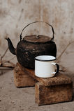 Sooty old teapot and white enamel mug on small wooden bench. Sooty old teapot and white enamel mug on small very old wooden bench Stock Image