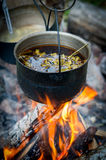 Sooty pot tourist hanging over the fire. Sooty pot with tea hanging over the fire Royalty Free Stock Photo