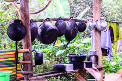 Sooty pots and pan hang on wooden bar at countryside.  Stock Photos