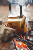 Sooty teapot is on fire. Metal sooty kettle stands on an open flame fire. Behind the rising white smoke royalty free stock photography