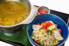 Sop Buntut, Traditional Indonesian food. Indonesian chicken soup or sop buntut, served in blue bowl with potatoe, eggs, bean sprouts and slice of tomato Stock Photography