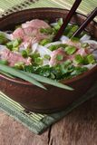 Sopa asiática com carne, macarronetes de arroz e as ervas frescas vertical fotos de stock royalty free