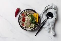 Sopa asiática com macarronete, carne e vegetais na bacia com o guardanapo no fundo branco com colher preta fotografia de stock royalty free