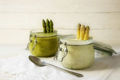 Sopa blanca y verde de la crema del espárrago en los tarros de cristal contra un bri Imagen de archivo