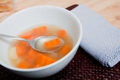 Sopa caliente en el tazón de fuente blanco Fotos de archivo libres de regalías