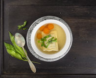 Sopa clara com ravioli, as cenouras e ramson alemães na placa de prata com colher do vintage Fotografia de Stock Royalty Free