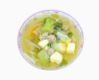 Sopa clara con la cuajada de habichuelas y el cerdo picadito en plato en el backg blanco Foto de archivo