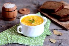 Sopa clara do arroz da galinha na bacia, guardanapo de matéria têxtil, folhas de louro, fatias do pão de centeio na tabela de mad Imagens de Stock