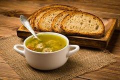 Sopa com almôndegas em uma bacia branca no fundo de madeira Imagens de Stock