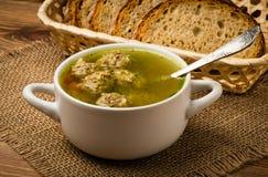 Sopa com almôndegas em uma bacia branca no fundo de madeira Imagens de Stock Royalty Free
