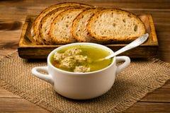 Sopa com almôndegas em uma bacia branca no fundo de madeira Imagem de Stock