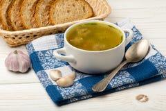 Sopa com almôndegas em uma bacia branca no fundo de madeira branco Imagens de Stock
