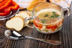 Sopa com carne da galinha, arroz, vegetais na bacia, guardanapo, partes de pão, pires com pimenta doce, colher na tabela imagem de stock royalty free