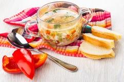 Sopa com carne da galinha, arroz, vegetais na bacia transparente no guardanapo, colher, partes de pão, pimenta doce na tabela de  imagem de stock royalty free