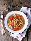 Sopa com galinha, grãos-de-bico, pimentas doces, cebolas, cenouras, aipo e salsa Alimento saudável Imagem de Stock