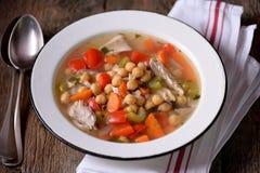 Sopa com galinha, grãos-de-bico, pimentas doces, cebolas, cenouras, aipo e salsa Alimento saudável Imagens de Stock