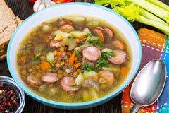 Sopa com lentilhas, aipo e salsichas na tabela de madeira velha Fotos de Stock Royalty Free