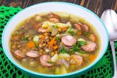 Sopa com lentilhas, aipo e salsichas na tabela de madeira velha Imagem de Stock