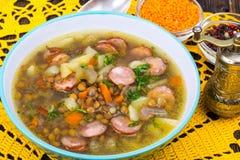 Sopa com lentilhas, aipo e salsichas na tabela de madeira velha Foto de Stock