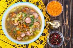 Sopa com lentilhas, aipo e salsichas na tabela de madeira velha Imagem de Stock Royalty Free