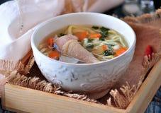 Sopa com macarronetes caseiros e a galinha orgânica com cenouras, raiz e folhas de varas da salsa, da cebola e de aipo Foto de Stock Royalty Free