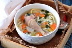 Sopa com macarronetes caseiros e a galinha orgânica com cenouras, raiz e folhas de varas da salsa, da cebola e de aipo Imagem de Stock Royalty Free