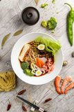 Sopa com marisco, macarronetes e vegetais em uma placa branca fotografia de stock