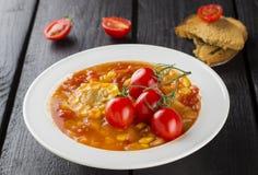 Sopa com milho e tomates na placa branca em um backgroun de madeira Imagens de Stock Royalty Free