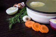 Sopa con el alazán, las verduras y el huevo hervido, cebolla roja, zanahorias, ajo, eneldo en la tabla de madera oscura Imágenes de archivo libres de regalías