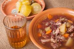Sopa con la haba y patata, pepinos salados y alcohol ilegal en un sa Fotografía de archivo