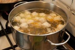 Sopa con las albóndigas en la cacerola en la estufa imágenes de archivo libres de regalías