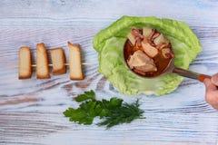 A sopa cozinhada no caldo da carne com ervas e o pão torrado frescos é derramada em uma placa com folha da couve imagem de stock royalty free