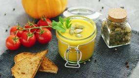 Sopa cremosa de la calabaza en tarro con pan y tomates almacen de video