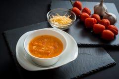 Sopa cremosa del tomate con queso contra fondo de madera negro Tostadas del pan, de los tomates de cereza, de las especias y del  Imágenes de archivo libres de regalías
