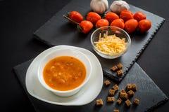 Sopa cremosa del tomate con queso contra fondo de madera negro Tostadas del pan, de los tomates de cereza, de las especias y del  Foto de archivo