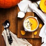 Sopa da abóbora com as sementes do chantiliy e de abóbora em um pla branco Fotos de Stock Royalty Free
