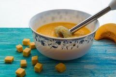 Sopa da abóbora com creme de leite e sementes em uma tabela de madeira de turquesa Foco seletivo, ainda vida, alimento e conceito Imagens de Stock