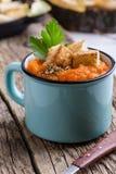 A sopa da abóbora de outono serviu na tabela de madeira em umas canecas rurais fotos de stock royalty free