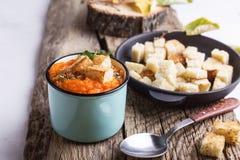 A sopa da abóbora de outono serviu na tabela de madeira em umas canecas rurais foto de stock royalty free