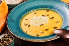 Sopa da abóbora e da cenoura com queijo parmesão, sementes de abóbora e pão no fundo de madeira escuro foto de stock