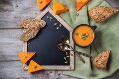 Sopa da abóbora em uma caneca na tabela rústica Imagem de Stock Royalty Free