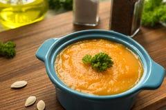 Sopa da abóbora na bacia com abóboras, alho e salsa frescos Imagens de Stock Royalty Free
