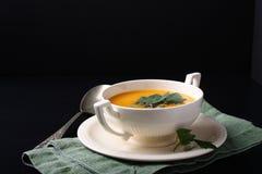 Sopa da abóbora na placa branca no fundo preto Foto de Stock Royalty Free