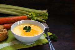 A sopa da cenoura com aipo, o creme e a salsa decoram em uma BO branca Foto de Stock Royalty Free