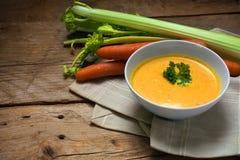 A sopa da cenoura com creme e a salsa decoram em uma bacia em w rústico Fotografia de Stock Royalty Free