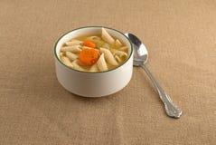 Sopa da massa de Penne em uma bacia com uma colher Fotografia de Stock Royalty Free