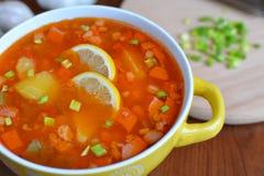 Sopa da mistura de Solyanka com salsichas, batatas e limão Fotos de Stock